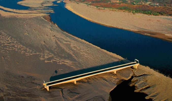 En fait, le pont était au bon endroit, ce fut un cyclone qui changeât le lit de la rivière. Parait-il qu'aujourd'hui les bretelles de raccordement ad hoc lui aurait rendu son utilité.