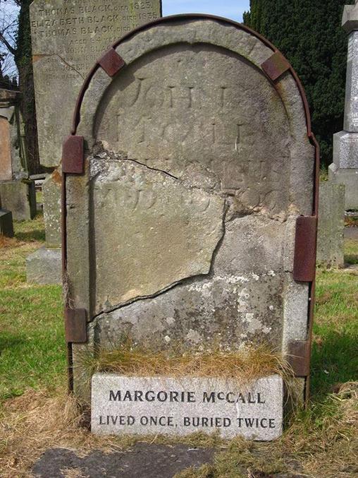 """Après avoir succombé à une sorte de fièvre en 1705, l'irlandaise Margorie McCall a été enterrée à la hâte pour empêcher la propagation de ce qu'on supposait contagieux. Margorie a été enterrée avec un anneau de valeur, que son mari n'a pas pu enlever à cause d'un gonflement des chairs. Cela a fait d'elle une cible toute trouvée pour les voleurs de corps. Le soir après l'enterrement de Margorie, avant même que la terre ne se tasse, les voleurs de tombe sont apparus et ont commencé à creuser. Incapables d'enlever l'anneau, ils ont décidé de couper le doigt. Dès que le sang a jailli, Margorie s'est réveillé de son coma, s'est assise bien droit droit et a crié. Le destin des voleurs de tombe reste inconnu. Une histoire dit qu'un des hommes est mort sur place de saisissement, tandis qu'une autre version affirme qu'ils ont fui et qu'ils ne sont jamais retournés à leur sale boulot. Margorie est sortie complètement du trou et est retournée chez elle. Son mari John, médecin, était à la maison avec les enfants quand il a entendu un coup à la porte. Il a dit aux enfants : ′′ Si votre mère était encore en vie, je jurerais que c'était son coup."""" Quand il ouvrit la porte pour trouver sa femme debout là, habillée de ses vêtements d'enterrement, du sang qui coulait du doigt mais qui était très vivante, il tomba raide mort au sol. Il fut enterré au même endroit que Margorie quelques jours auparavant. Margorie se remaria et eut d'autres enfants. Quand elle est finalement morte naturellement, elle a été renvoyée au cimetière Shankill à Lurgan, en Irlande, où se trouve toujours sa pierre tombale. Il porte l'inscription """"A vécu UNE fois, a été enterrée DEUX fois""""."""