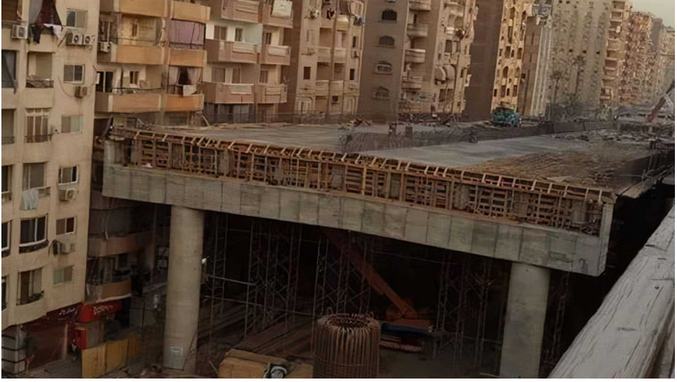 Au Caire, en Egypte, un pont autoroutier est en construction au milieu de barres d'immeubles et il passe à seulement 50 cm des balcons des résidents !   Ce projet délirant est défendu par les autorités qui expliquent que plusieurs immeubles ont été construits de manière illégale, ce que les propriétaires réfutent, bien évidemment. Ils précisent que quatre d'entre eux seront détruits à la fin des travaux car ils constituent un obstacle. Un comité a été formé afin d'enquêter sur tous les bâtiments pour déterminer ceux qui n'ont pas été autorisés à sortir de terre (certains permis de construire datent de 2018). Une indemnisation est prévue pour les résidents lésés par la situation et qui devront se reloger.   Ce projet fou mesure 12 km de long et jusqu'à 65,5 m de large. Il a coûté plusieurs centaines de millions d'euros aux autorités qui mettent l'accent sur son importante cruciale dans une ville particulièrement embouteillée.