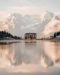 Belle photo : un grand hôtel des Alpes se mire dans un lac