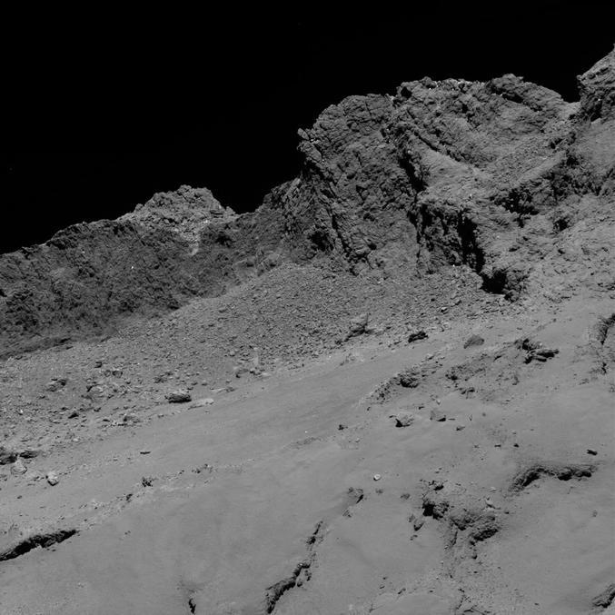 Une des dernières photos de la comète 67P Churyumov-Gerasimenko prises par Rosetta lors de sa descente, montrant la surface poussiéreuse de la région Maat, et quelques falaises en arrière-plan  Image prise à 16 km de la surface, s'étendant sur environ 614 m de large (~30 cm/pixel, pour vous donner une idée de la taille des rochers qu'on y voit.)