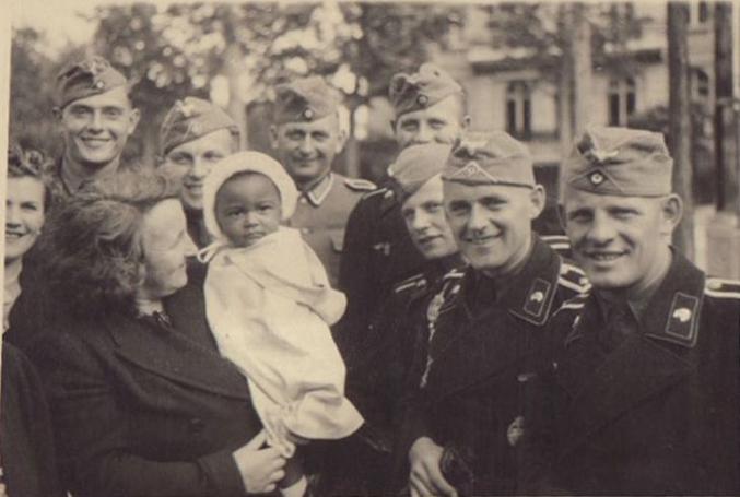 Dans la France occupée, quelques soldats allemands (dont des tankistes à l'uniforme noir) posent auprès d'un bébé euh... surexposé.