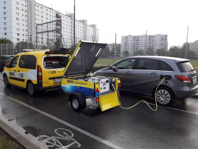 Image futuriste d'un véhicule diesel remorquant une batterie pour recharger un véhicule électrique.
