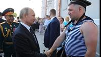 Poutine serre la main à un marin russe à l'uniforme approximatif (pas de vareuse, pas d'insigne...)