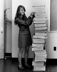 Margaret Hamilton, ingénieur logiciel sur le projet Apollo posant avec son code source