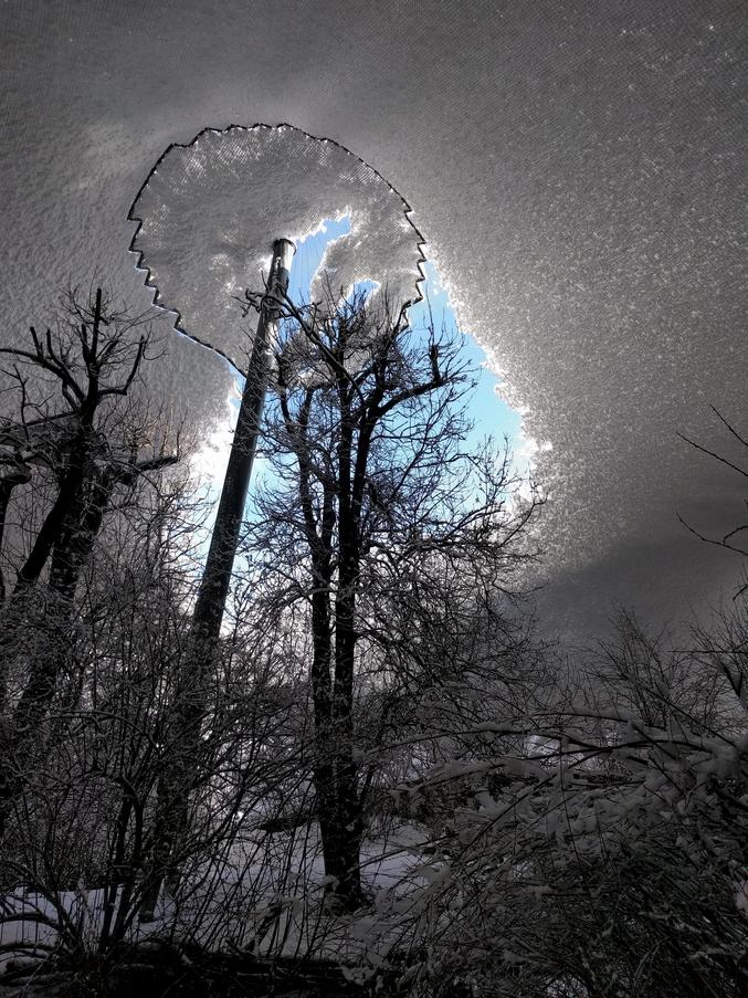 La neige s'est accumulée sur ce filet recouvrant une immense volière.