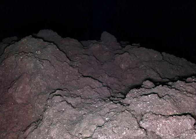 Photo a priori sans le moindre intérêt d'un rocher, la nuit. Sauf que ce rocher est l'astéroïde Ryugu, qui orbite actuellement à 340 millions de kilomètres de la Terre, immortalisé par le petit robot franco-allemand Mascot.