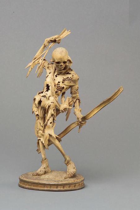 Sculpture de 1520 en Allemagne, réalisée en bois de poirier (non savant), représentant la Mort avec des flèches dans la main droite levée, un arc dans la main gauche et un carquois autour du cou. Les côtes et les os sont partiellement exposés, la peau et les restes de vêtements pendent en lambeaux du squelette. La posture inhabituelle et la rotation dynamique du corps ont contribué à attribuer la sculpture au sculpteur de Landshut Hans Leinberger.  Source : https://www.khm.at/objektdb/detail/390919/