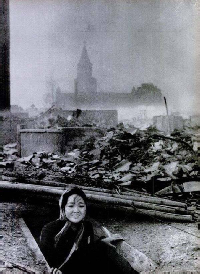 """Une survivante de Nagasaki sort de son abri en souriant. Beaucoup de survivants mourront dans les 72h, des suites des radiations. On aperçoit derrière l'église de Nagasaki, épargnée. La ville abritait la plus grosse communauté catholique du Japon. D'ailleurs, une des premières choses remises en place sera une cloche qui appellera les fidèles à la prière des heures, remise sur pieds par un monastère voisin. Lire à ce sujet """"Les cloches de Nagasaki"""" de Takashi-Paul Nagaï (qui est un type assez extraordinaire)."""