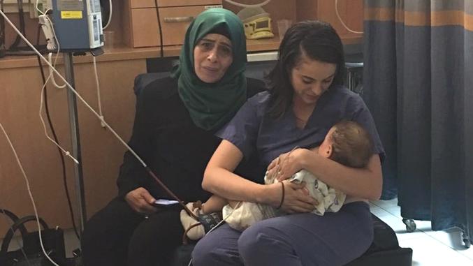 Allaitant l'enfant d'une femme palestienne, trop malade pour le faire elle-même.