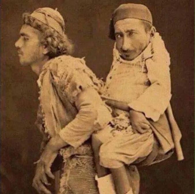 """ca traînait sur Facebook. Pas sûr que ça soit vrai, mais l'histoire est belle.  """"Cette photo est réelle , elle fut prise à Damas en 1899 : le nain handicapé c'est Samir il est chrétien et incapable de marcher , celui qui le porte sur son dos c'est Mohamed , il est musulman et aveugle et compte sur Samir pour lui indiquer le chemin tandis que Samir se sert du dos de son ami pour se déplacer dans le rues de la ville. Ils étaient tous deux orphelins et sans famille et logeaient dans la même chambre. Samir était hakawati , il avait le don de la narration et racontait des contes de mille et une nuits aux clients d'un café de Damas , Mohamed quant à lui vendait les bolbolas devant le même café et se plaisait à écouter les histoires de son ami. Quand le chrétien est mort , son ami se retira dans sa chambre où on le trouva mort après avoir pleuré son compagnon sept jours de suite""""."""