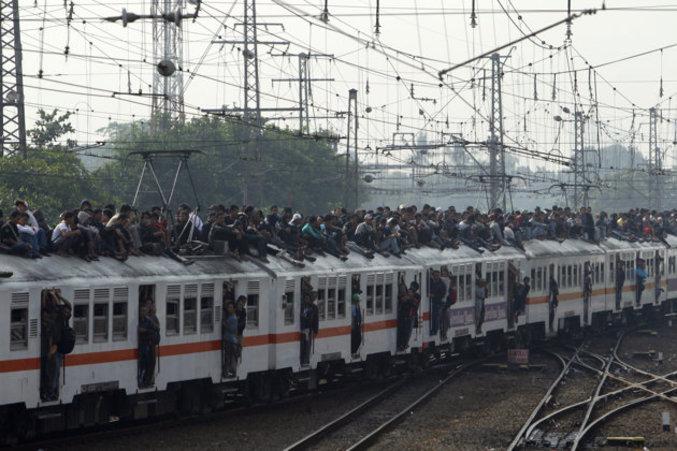 Des passagers se tiennent assis sur le toit d'un train à l'entrée en gare Manggarai de Jakarta. Le système ferroviaire indonésien va être sujet à modernisation dans les prochaines semaines.