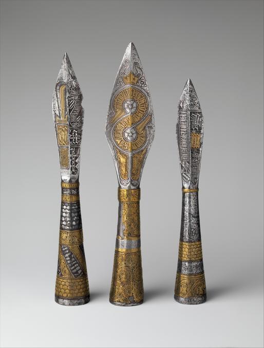 Réalisées en mélange de cuivre et d'étain en Bohème au XVe siècle, elles étaient à l'origine fichées sur des bâtons et servaient probablement de marques de rang ou de bâton de commandement. Elles sont décorées de monogrammes et d'insignes royaux de Bohême, en plus d'inscriptions religieuses en tchèque médiéval. Toutes trois portent le monogramme AR pour Albert, roi de Bohême et de Hongrie de 1437 à 39, et l'une porte aussi le monogramme AE, probablement pour Albert et Elizabeth, sa reine.  Les pointes de flèche droite et gauche sont estampillées de la marque dite de l'arsenal turc, indiquant qu'elles ont été capturées par les forces ottomanes, peut-être lors de la campagne de 1439 au cours de laquelle Albert a été tué, et ont ensuite été stockées dans l'arsenal turc de Constantinople (actuelle Istanbul).  Source et plus de photos ici : https://www.metmuseum.org/art/collection/search/35794