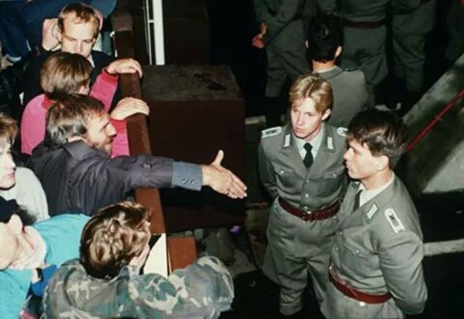 Des vopos (Volkspolizei, policiers allemands de RDA) refusent de serrer la main des manifestants ouest-Berlinois, lors de la chute du mur.